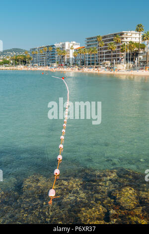 Early morning unidentifiable sun bathers and swimming at the Juan les Pins beach, a popular resort destination on the Mediterranean - Stock Photo