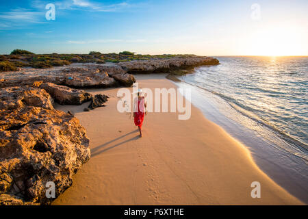 Osprey Bay, Cape Range National Park, Exmouth, Western Australia, Australia. Woman with elegant red dress and straw hat admiring the sunsset (MR). - Stock Photo