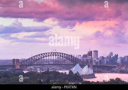 View of Sydney Harbour Bridge and Sydney Opera House at sunset, Sydney, New South Wales, Australia - Stock Photo