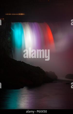 Canada and USA, Ontario and New York State, Niagara, Niagara Falls, Horseshoe Falls illuminated at night - Stock Photo