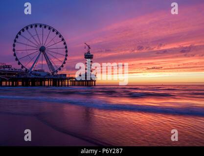 Pier and Ferris Wheel in Scheveningen, sunset, The Hague, South Holland, The Netherlands - Stock Photo