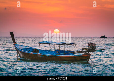 Longtail boats at Sunset Beach, Ko Lipe, Satun Province, Thailand. Traditional long tail boat and rising sun. - Stock Photo