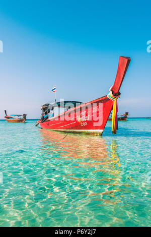 Ko Lipe, Satun Province, Thailand. Red wooden long tail boat on turquoise water. - Stock Photo