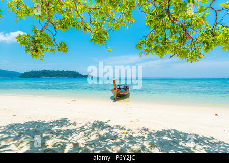 Ko Lipe, Satun Province, Thailand. Traditional long tail boat moored on an empty beach. - Stock Photo