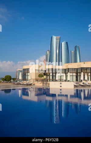 United Arab Emirates, Abu Dhabi, United Etihad Towers reflecting in outdoor swimming pool at Intercontental Hotel - Stock Photo