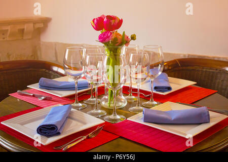 Empty glasses set in restaurant,  detail of a dining table set up with wine glasses. - Stock Photo