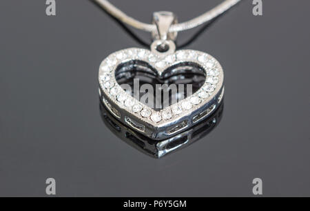 Silver jewelry pendant with diamond on dark background / silver jewelry / necklaces with heart pendants on black background / necklaces with heart pen - Stock Photo