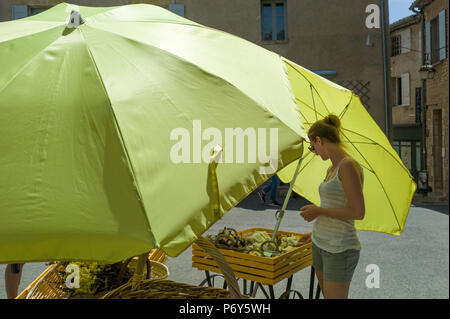 Woman buying goods from a stall  which is protected two Large Umbrellas Gordes Provence - Stock Photo