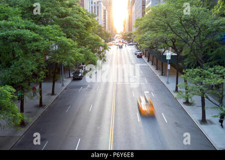 New York City taxi speeding down 42nd Street in Midtown Manhattan with the sunset in the background - Stock Photo