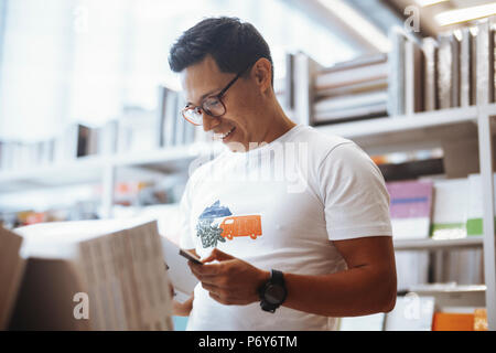 Young happy spectacled man reading book in bright modern book store. - Stock Photo