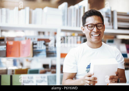 Young happy spectacled man holding book with blank cover and laughing. - Stock Photo