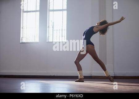 Graceful young female dancer practicing in dance studio - Stock Photo