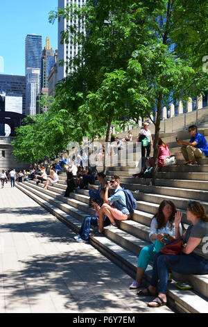 People take a mid day break under the trees on the stadium steps of the Chicago Riverwalk section known as the River Theater. - Stock Photo
