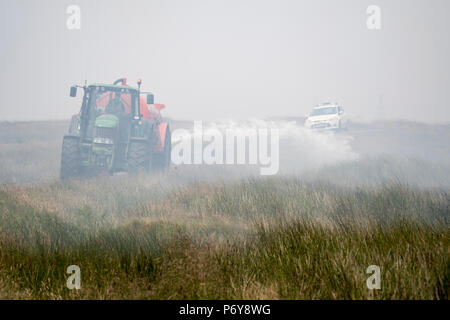 1 July 2018 - Local farmers donated water trucks to spread water around the Winter Hill area. Fire crews from across the UK have converged on Winter Hill to control the blaze which is growing by metres per hour. Lancashire Fire and Rescue and Lancashire Police are leading the response to the 'major incident'. - Stock Photo