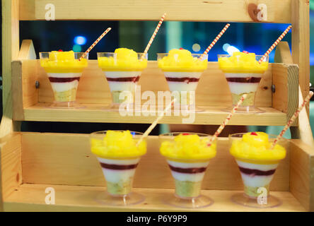 Selective focus photo of Seasonal Tropical Mango Fruit creamy trifle in beautiful glasses with fresh ripe fruit slices on table background. Delicious  - Stock Photo