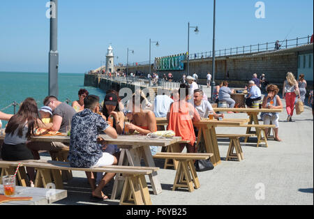 People enjoying a drink the sun, at the waterside tables, on the seafront  harbour arm at Folkestone Harbour, Kent, UK - Stock Photo