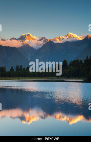 New Zealand, South Island, West Coast, Fox Glacier Village, Lake Matheson, reflection of Mt. Tasman and Mt. Cook, dusk - Stock Photo