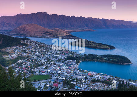 New Zealand, South Island, Otago, Queenstown, elevated town view with The Remarkables from the Skyline Gondola deck, dusk - Stock Photo