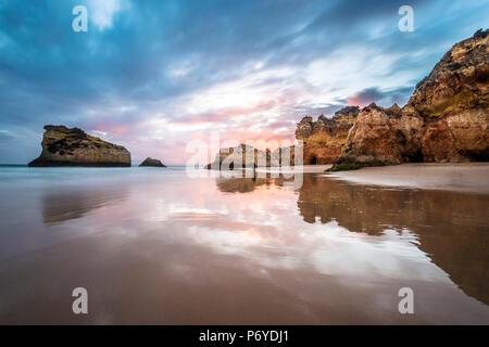 Praia da Rocha, Portimao, Algarve, Portugal. Sunset over the iconic rock formations along the coast. - Stock Photo