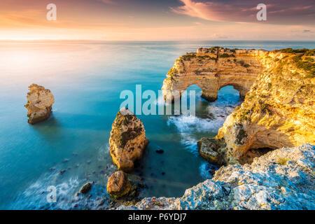 Praia de Marinha, Caramujeira, Lagoa, Algarve, Portugal. Coastal rock formations at sunrise. - Stock Photo