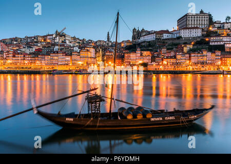Traditional Rabelo boat designed to carry wine down Douro river with city skyline behind, Porto, Portugal - Stock Photo