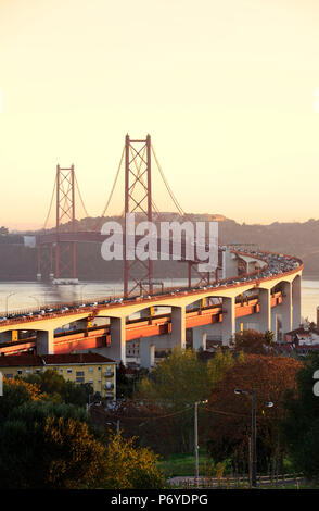 25 de April bridge (similar to the Golden Gate bridge) across the Tagus river, in the evening. Lisbon, Portugal - Stock Photo