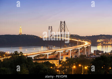 25 de April bridge (similar to the Golden Gate bridge) across the Tagus river and Cristo Rei (Christ the King) on the south bank of the river, in the evening. Lisbon, Portugal - Stock Photo