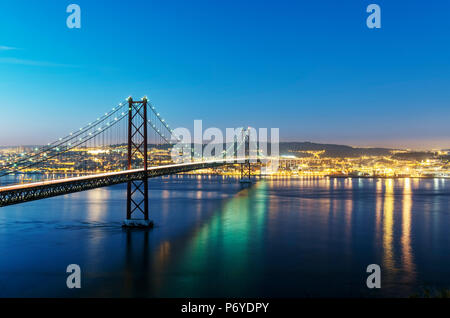 25th of April Bridge over the Tagus river (Tejo river) and Lisbon at twilight. Portugal - Stock Photo