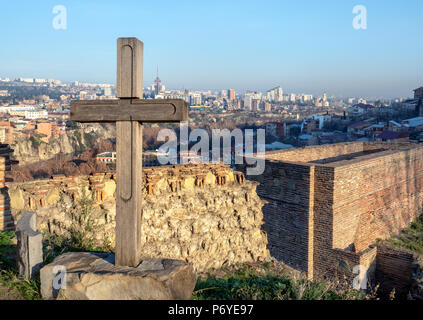Old wooden cross overlooking Tbilisi skyline, Georgia - Stock Photo