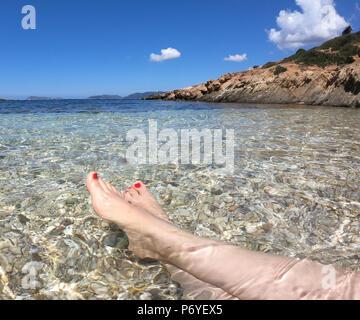 Legs relaxing on  sardinia beach in italy - Stock Photo