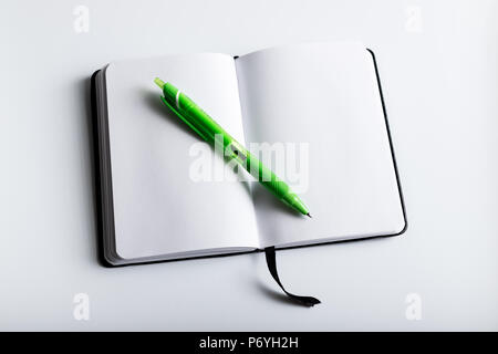 Open empty note book with green pen on white background shot above - Stock Photo