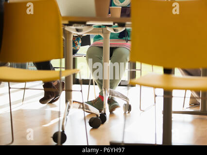 Legs of businesswoman under conference room table - Stock Photo