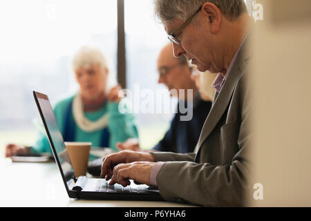 Focused senior businessman using laptop in conference room meeting - Stock Photo