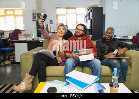 Happy creative business people taking selfie in casual open plan office - Stock Photo