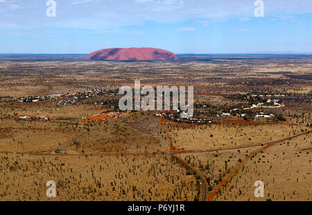 Aerial view of  the town of Yulara with Uluru in the background - Stock Photo