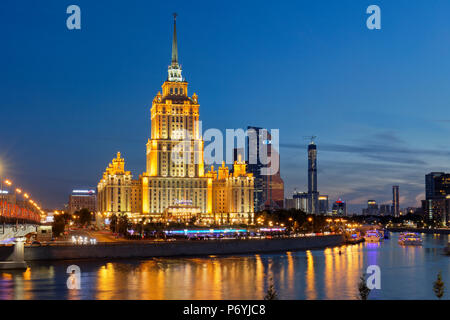 Radisson Royal Hotel Stalinist style high-rise building on Moskva River illuminated at dusk. Moscow, Russia. - Stock Photo