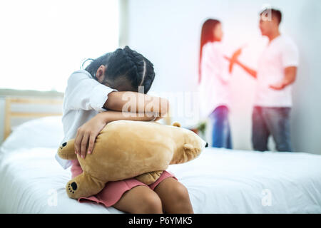 The unhappy girl sitting near the arguing parents on the bed - Stock Photo