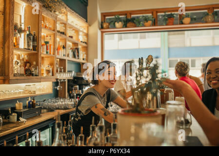 Smiling female bartender talking with customers at a bar counter - Stock Photo