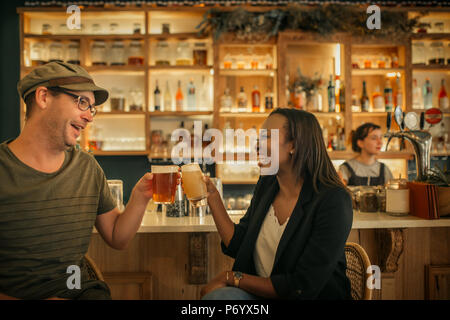 Two smiling young friends cheering with drinks in a bar  - Stock Photo