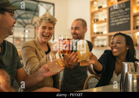 Friends hanging out together in a bar cheering with drinks  - Stock Photo