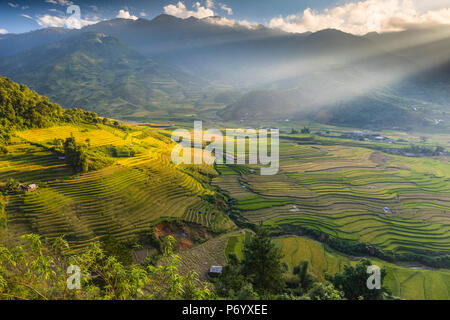 Sun beams over the mountains surrounding the rice terraces at Tu Le, Yen Bai Province, Vietnam, South-East Asia - Stock Photo