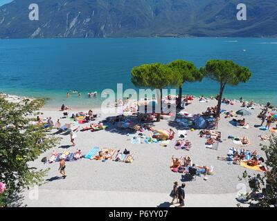 Limone sul Garda, Italy - August 2016: People having fun and relax on the beach at Garda Lake - Stock Photo