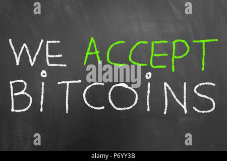 We accept bitcoins chalk text written on blackboard or chalkboard as cryptocurrency virtual payment concept - Stock Photo