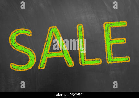 Sale chalk text advertisement on blackboard or chalkboard as shopping price deduction discount concept - Stock Photo
