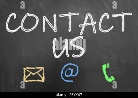 Contact us chalk text on blackboard or chalkboard as customer support service and public relation concept - Stock Photo