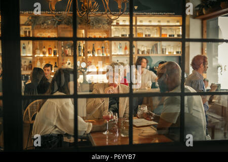 Diverse young friends having drinks together at a trendy bar - Stock Photo