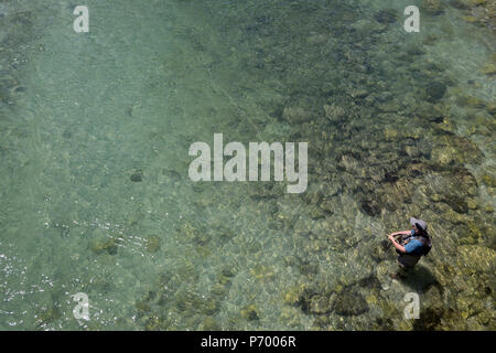 A fly-fisherman casts off in clear waters of the Sava Bohinjnka river, on 18th June 2018, in Bohinjska Bela, Bled, Slovenia. - Stock Photo