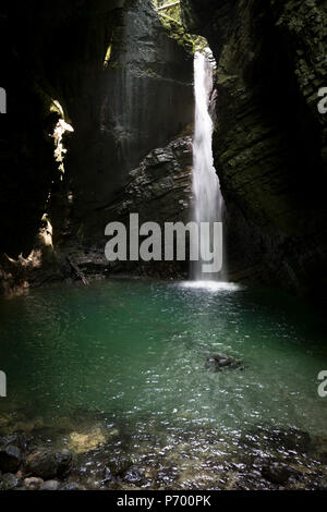 Adventurous walkers negotiate moderate terrain in the rocky gorge near the 15m high Kozjak Waterfalls, part of the Kobarid Heritage Trail, on 21st June 2018, in Kobarid, Slovenia. - Stock Photo