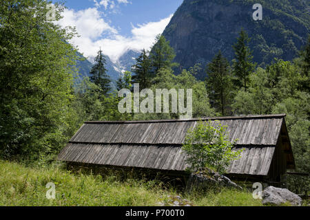 With the highest peaks in Slovenia in the distance is a traditional Slovenian mountain hut in the Slovenian Julian Alps, on 22nd June 2018, in Trenta, Triglav National Park, Slovenia. Beyond are the mountains, Kreiski 2050m, Pihavec 2419m, Dolina Zadnjica and Triglav 2864m. - Stock Photo
