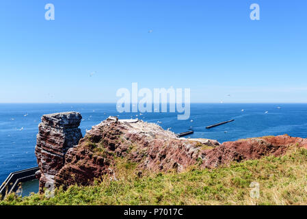 Lange Anna sea stack rock on Helgoland island against blue sea on clear day - Stock Photo